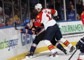 Filip Kuba of the Florida Panthers hits John Tavares of the New York Islanders into the boards at the Nassau Veterans Memorial Coliseum on March 24...