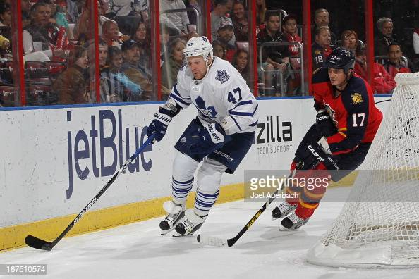 Filip Kuba of the Florida Panthers pursues Leo Komarov of the Toronto Maple Leafs as he skates behind the net with the puck at the BBT Center on...