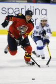 Filip Kuba of the Florida Panthers skates with the puck as Martin St Louis of the Tampa Bay Lightning chases during a NHL game against the Florida...