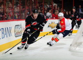 Filip Kuba of the Florida Panthers trails Alexander Semin of the Carolina Hurricanes behind the net as Eric Staal looks on during an NHL game on...