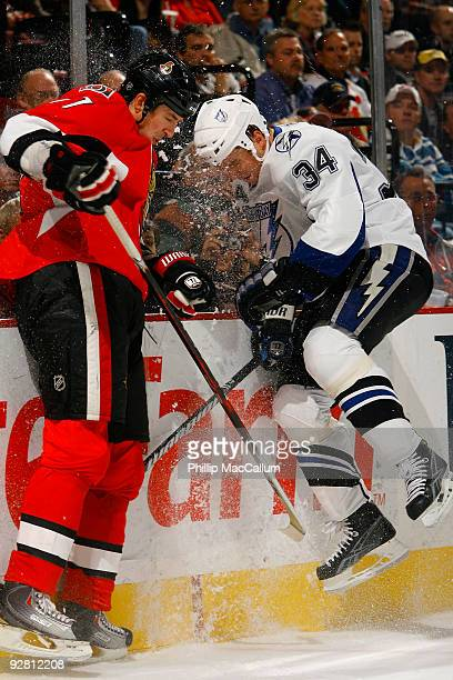 Filip Kuba of the Ottawa Senators and Ryan Craig of the Tampa Bay Lightning crash into the end boards during a game at Scotiabank Place on November 5...