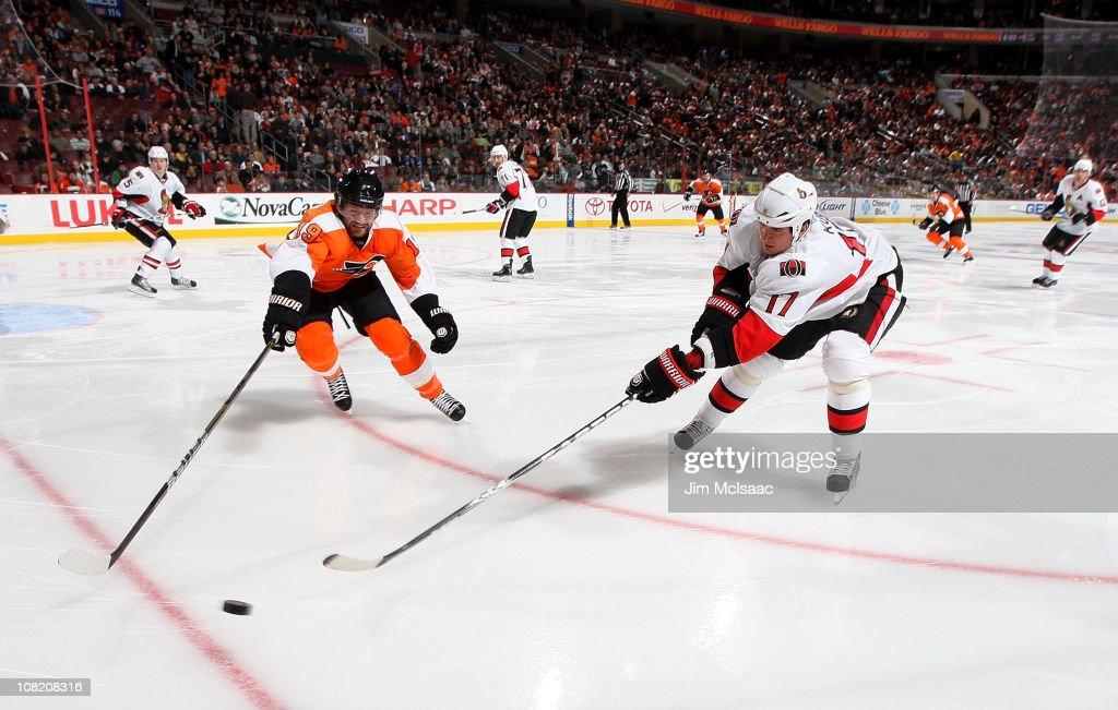 <a gi-track='captionPersonalityLinkClicked' href=/galleries/search?phrase=Filip+Kuba&family=editorial&specificpeople=209425 ng-click='$event.stopPropagation()'>Filip Kuba</a> #17 of the Ottawa Senators reaches for the puck against <a gi-track='captionPersonalityLinkClicked' href=/galleries/search?phrase=Scott+Hartnell&family=editorial&specificpeople=201889 ng-click='$event.stopPropagation()'>Scott Hartnell</a> #19 of the Philadelphia Flyers on January 20, 2011 at Wells Fargo Center in Philadelphia, Pennsylvania.