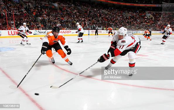 Filip Kuba of the Ottawa Senators reaches for the puck against Scott Hartnell of the Philadelphia Flyers on January 20 2011 at Wells Fargo Center in...