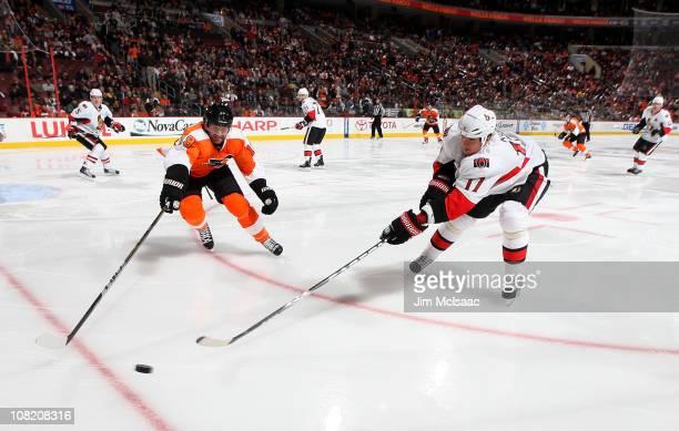 Filip Kuba of the Ottawa Senators reaches for the puck against Scott Hartnell of the Philadelphia Flyers on January 20 2011 at Wells Fargo Center in...