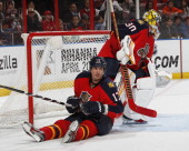 Filip Kuba slides past goaltender Scott Clemmensen of the Florida Panthers and knocks the goal off the supports during second period action against...