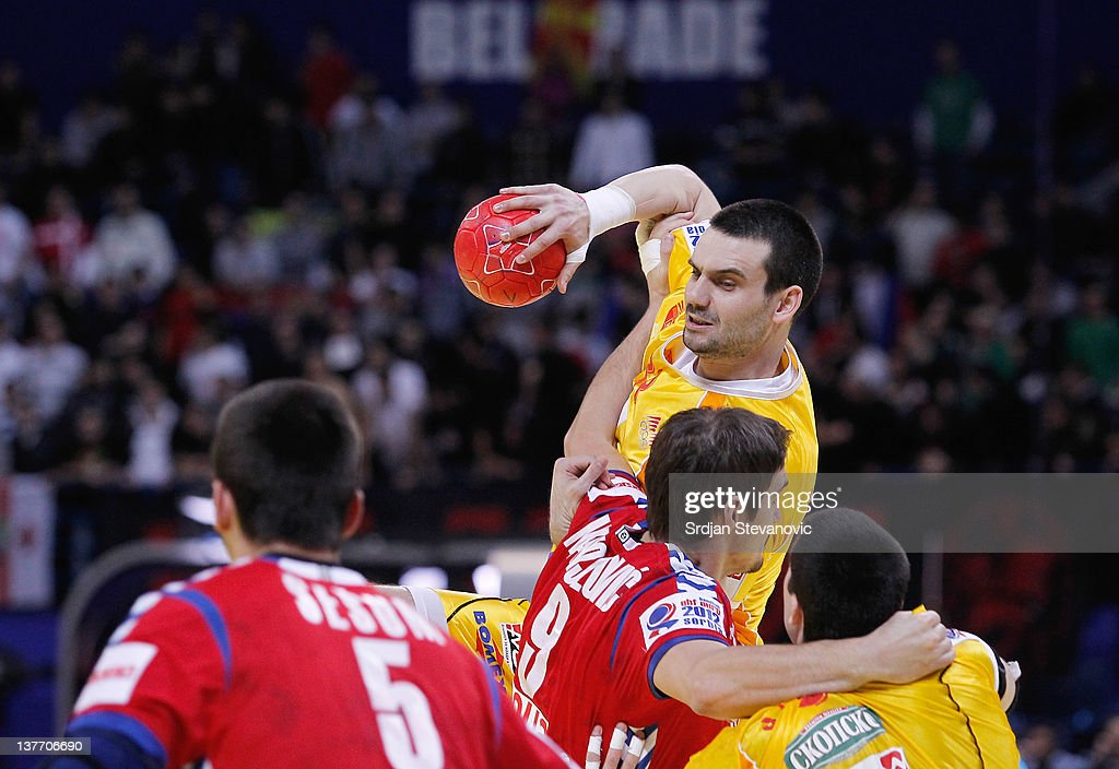 Filip Lazarov (C) of Macedonia holds the ball as he competes with Nikola Manojlovic (number 9) of Serbia during the Men's European Handball Championship 2012 second round group one match between Serbia and Macedonia at Arena Hall on January 25, 2012 in Belgrade, Serbia.