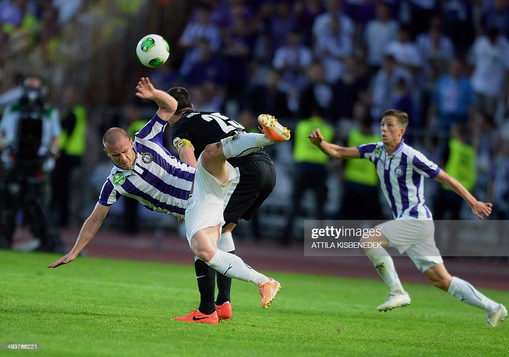 Filip Stanisavljevic (L) of TE Ujpest is fouled by Akos Elek (C) of VTK Disosgyor during the Hungarian Cup final football match VTK Disosgyor vs TE Ujpest on May 25, 2014 at the Puskas stadium in Budapest.