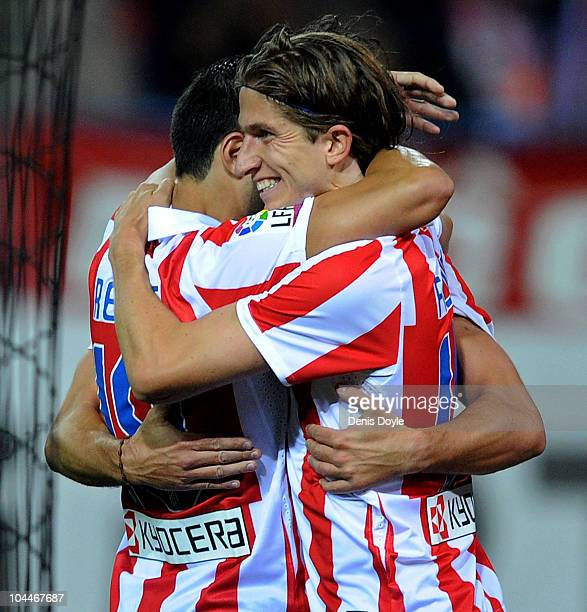 Felipe Luis celebrates with Jose Antonio Reyes of Atletico Madrid after Atletico Madrid scored their first goal during the La Liga match between...