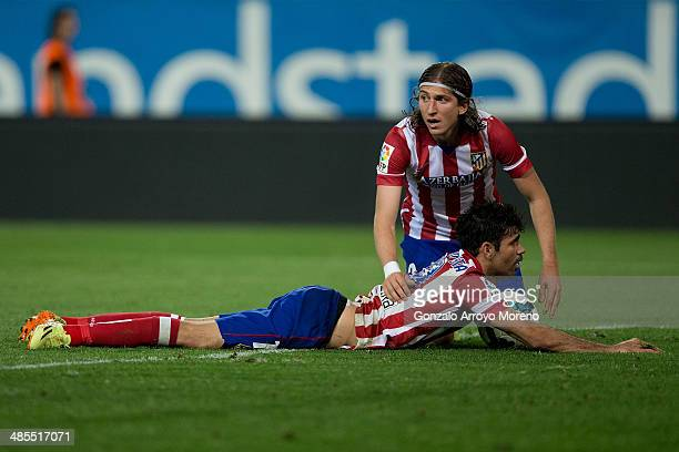 Filipe Luis of Atletico de Madrid assists his teammate Diego Costa after being tackled by Cristian Sapunaru of Elche FC during the La Liga match...