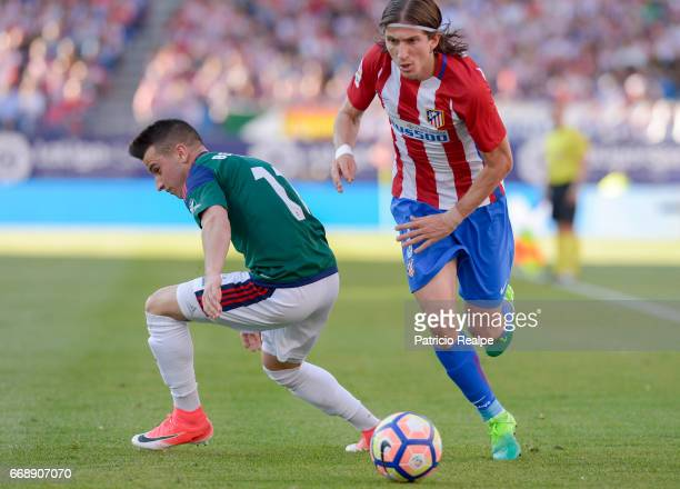 Filipe Luis of Atletico de Madrid figths the ball with Alejandro Berenguer of Osasuna during the match between Atletico Madrid v Osasuna as part of...