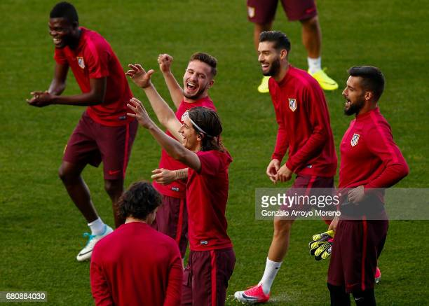 Filipe Luis of Atletico de Madrid jokes with teammates Thomas Teye Partey Saul Niguez and Yannick Carrasco during a training session ahead of the...