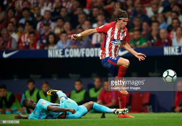 Filipe Luis of Atletico Madrid is tackled by Nelson Semedo of Barcelona during the La Liga match between Atletico Madrid and Barcelona at Estadio...
