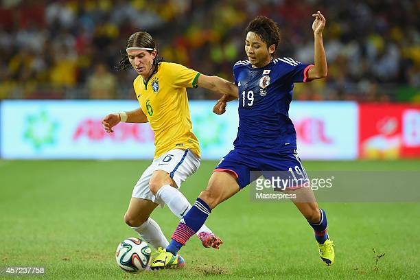 Filipe Luis of Brazil and Yu Kobayashi of Japan compete for the ball during the international friendly match between Japan and Brazil at the National...