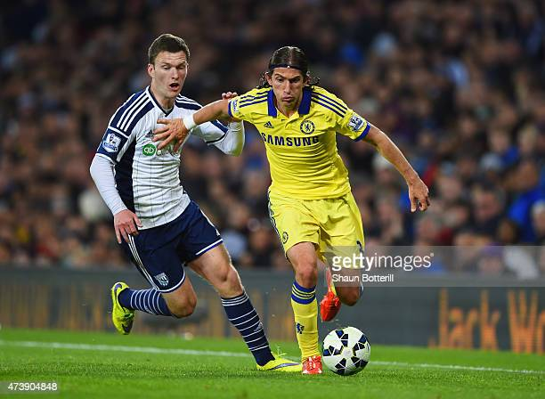 Filipe Luis of Chelsea holds off Craig Gardner of West Bromwich Albion during the Barclays Premier League match between West Bromwich Albion and...