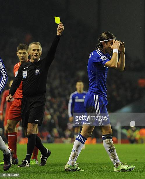 Filipe Luis of Chelsea is shown the yellow card by Referee Martin Atkinson during the Capital One Cup SemiFinal First Leg between Liverpool and...