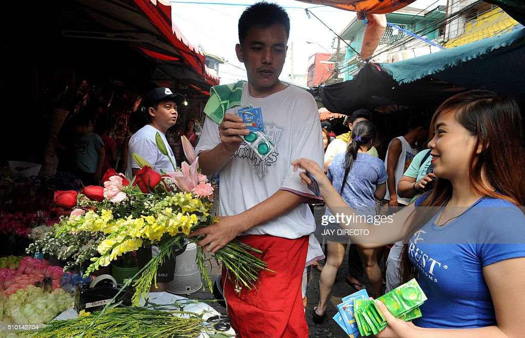 A Filipina (R) hands out free condoms to a man buying flowers at a flower market as part of a promotion on Valentine's Day in Manila on February 14, 2016. Although not an official holiday, Valentine's Day is widely celebrated in this largely Christian nation with acts of affection and romance such as sweethearts going on special dates or giving expensive presents. AFP PHOTO / Jay DIRECTO / AFP / JAY DIRECTO
