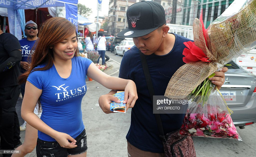 A Filipina (L) hands out free condoms to a man buying flowers at a flower market as part of a promotion on Valentine's Day in Manila on February 14, 2016. Although not an official holiday, Valentine's Day is widely celebrated in this largely Christian nation with acts of affection and romance such as sweethearts going on special dates or giving expensive presents. AFP PHOTO / Jay DIRECTO / AFP / JAY DIRECTO