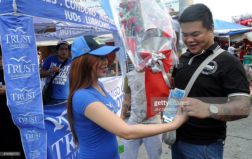 A Filipina hands out free condoms to a man buying flowers at a flower market as part of a promotion on Valentine's Day in Manila on February 14, 2016. Although not an official holiday, Valentine's Day is widely celebrated in this largely Christian nation with acts of affection and romance such as sweethearts going on special dates or giving expensive presents. AFP PHOTO / Jay DIRECTO / AFP / JAY DIRECTO