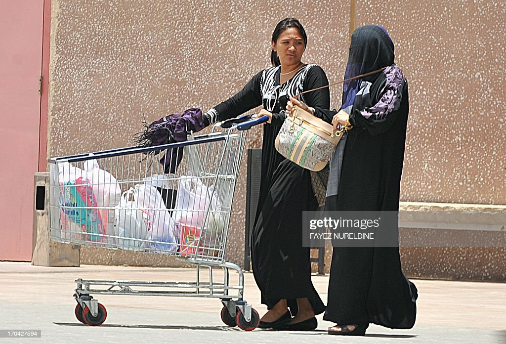 A Filipina maid talks to her employer as she pushed a shopping trolley outside a mall in Riyadh, on June 12, 2013. A three-month reprieve ended for Fhilipino death row convict Joselito Zapanta, who risks execution in Saudi Arabia for having failed to raise nearly $1 million in 'blood money' to pay the kin of his murdered landlord.