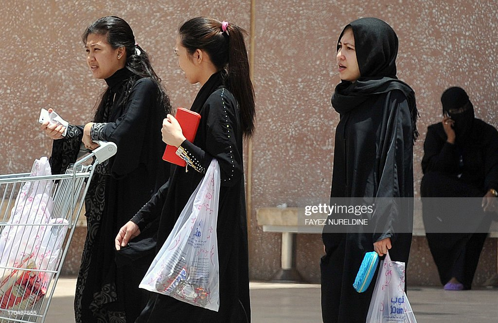 Filipina maids carry shopping bags as they walk out of a mall in Riyadh, on June 12, 2013. A three-month reprieve ended for Fhilipino death row convict Joselito Zapanta, who risks execution in Saudi Arabia for having failed to raise nearly $1 million in 'blood money' to pay the kin of his murdered landlord. AFP PHOTO/FAYEZ NURELDINE