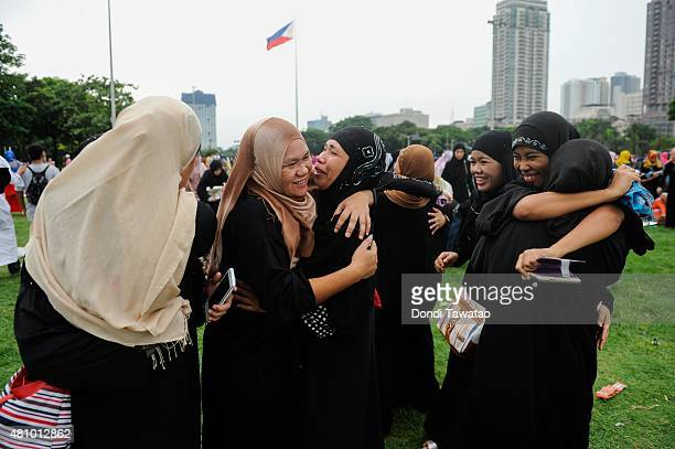 Filipina Muslims hug each other after prayer as they ended Ramadan on July 17 2015 in Manila Philippines Muslims in the Philippines join their...