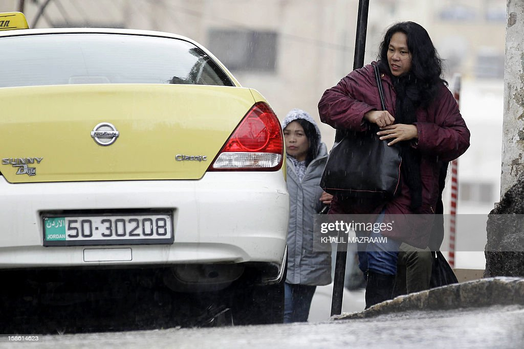 Filipina woman residing in Jordan walks past a taxi near central Amman on December 21, 2012. In October, the Philippines lifted a ban imposed in 2007 on its citizens working in Jordan after the two countries signed deals to protect them, including guaranteeing a minimum monthly salary of $400. The ban had been imposed because of 'the growing number of distressed Filipino workers' seeking help from diplomatic offices in Jordan, according to Manila. But despite the accords, abuse is still reported. AFP PHOTO/KHALIL MAZRAAWI