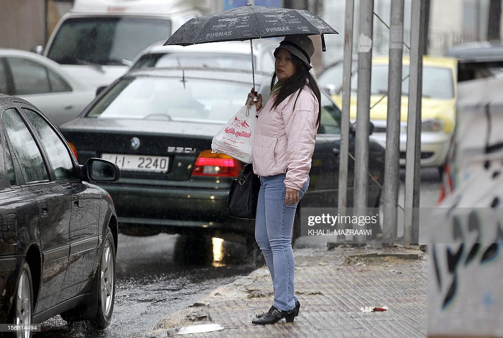 Filipina woman residing in Jordan walks under the rain with an umbrella near central Amman on December 21, 2012. In October, the Philippines lifted a ban imposed in 2007 on its citizens working in Jordan after the two countries signed deals to protect them, including guaranteeing a minimum monthly salary of $400. The ban had been imposed because of 'the growing number of distressed Filipino workers' seeking help from diplomatic offices in Jordan, according to Manila. But despite the accords, abuse is still reported. AFP PHOTO/KHALIL MAZRAAWI