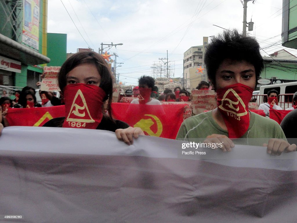 Filipino activists from the communist youth group Kabataang Makabayan hold flags and placards as they shout slogans during a 'lightning rally' in...