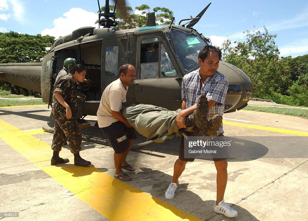 Filipino army soldiers carry the remains of Filipino Scout Ranger 1Lt Jessie James Apura upon arrival in army headquarters June 27 2002 in Zamboanga...