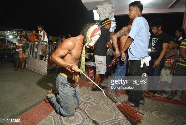 Filipino Catholic devotees flagellate themselves with wooden flails on Holy Thursday on April 5 2012 in Manila Philippines Flagellation is an extreme...
