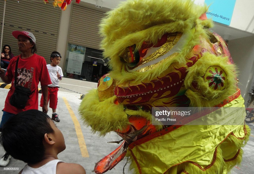 Filipino child looks at a dragon dancer in Manila's Chinatown. This year marks the Year of the Fire Monkey in Chinese astrology.