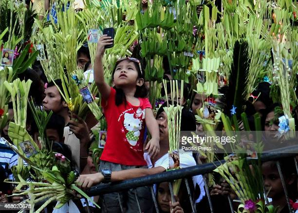 Filipino child records devotees waving palm fronds during mass on Palm Sunday at the Baclaran Church Palm Sunday marks the triumphant entry of Jesus...