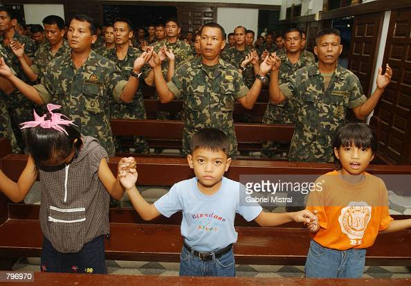 Filipino children join Philippine marines attending a thanksgiving mass June 22 2002 at Navy headquarters in the southern port city of Zamboanga...