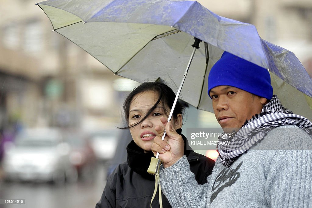 Filipino couple residing in Jordan walk under the rain with an umbrella near central Amman on December 21, 2012. In October, the Philippines lifted a ban imposed in 2007 on its citizens working in Jordan after the two countries signed deals to protect them, including guaranteeing a minimum monthly salary of $400. The ban had been imposed because of 'the growing number of distressed Filipino workers' seeking help from diplomatic offices in Jordan, according to Manila. But despite the accords, abuse is still reported.