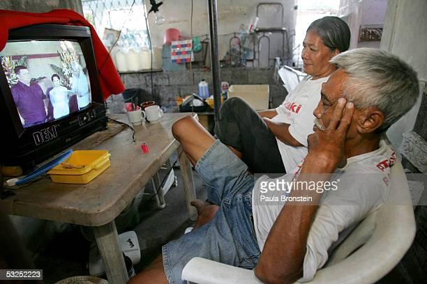 Filipino couple watch President Gloria MacapagalArroyo on TV inside their tomb turned home at the North Cemetery on July 16 2005 in Manila...