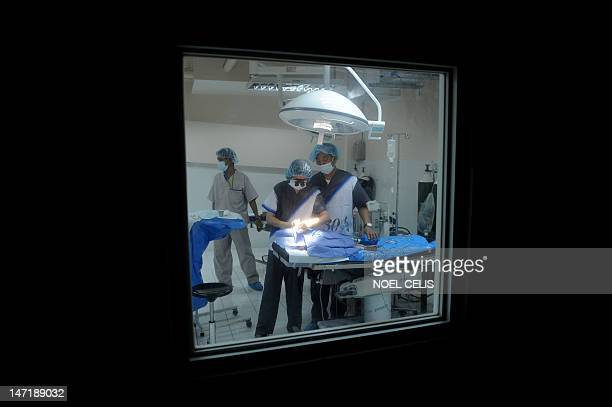 Filipino doctors are pictured in the operating theatre as they perform surgery on toddler Mark Carlos Nuegas to repair his cleft palate during a...