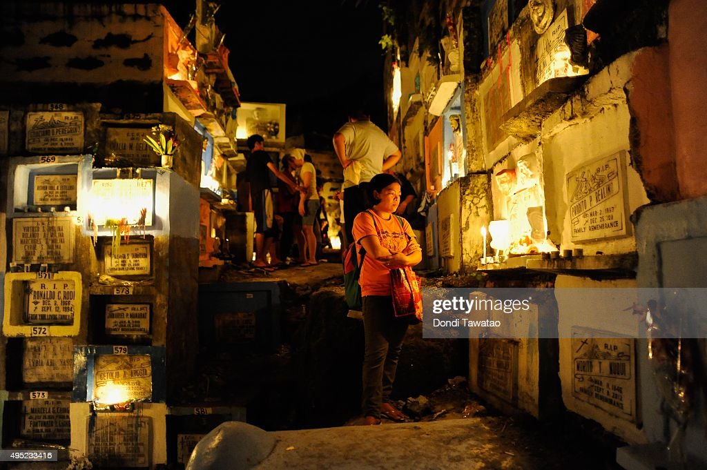 Filipino families light candles and pray on november 1 2015 in manila
