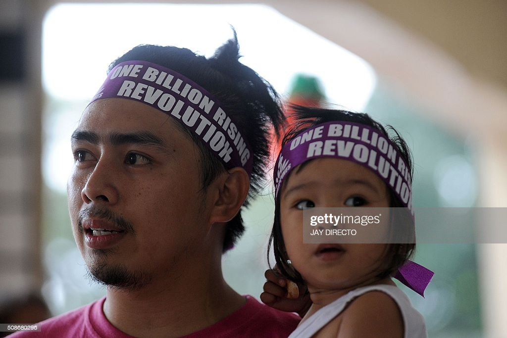 A Filipino father and his child attend a dance exercise in suburban Manila on February 6, 2016, to draw attention to sexual abuse of women and children as part of the 'One Billion Rising' campaign against such abuse. Forced prostitution and the use of children in online child pornography are major concerns in the impoverished nation. AFP PHOTO / Jay DIRECTO / AFP / JAY