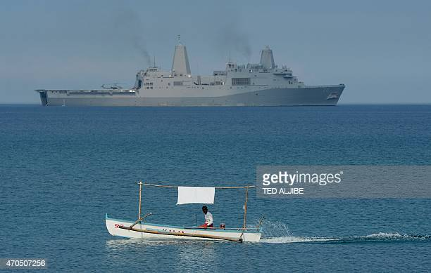 A Filipino fisherman is seen past the US Navy amphibious transport dock ship USS Green Bay during an amphibious landing exercise on a beach at San...