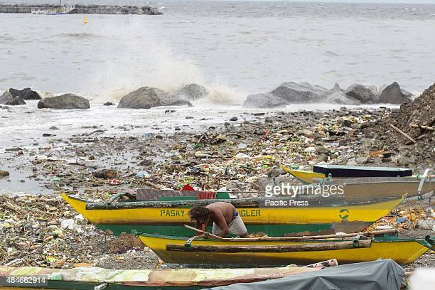 Filipino fisherman prepares to dock his boat as waves crash by the shore in Pasay City south of Manila Typhoon Goni packing maximum winds of 180...