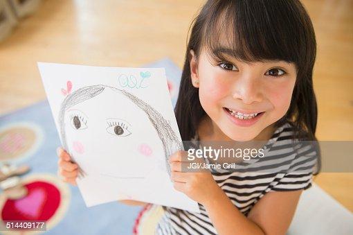 Filipino girl displaying drawing in bedroom
