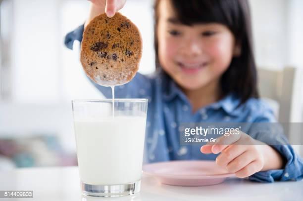 Filipino girl dunking cookie in milk