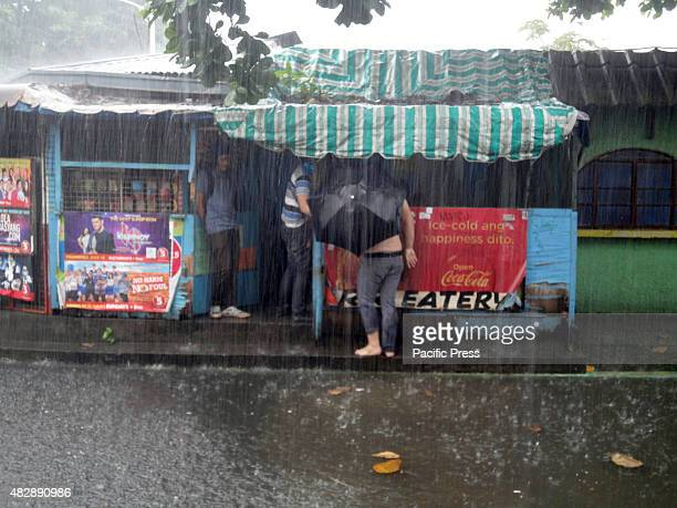 Filipino holding a black umbrella walks along a narrow path leading to an eatery in suburban Quezon City east of Manila Philippines to avoid...