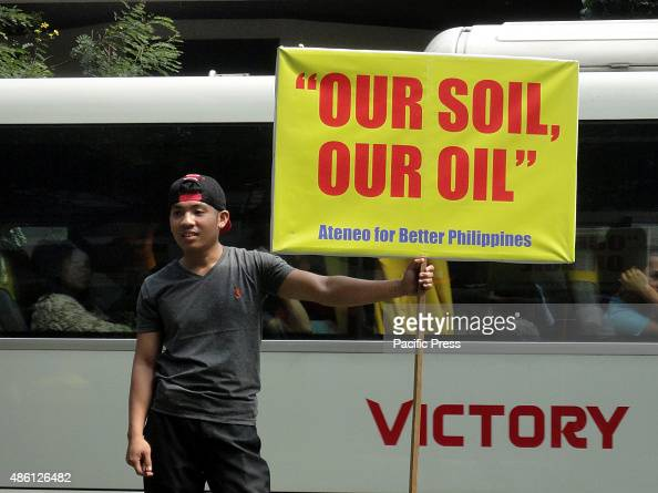 Filipino holds a placard during a rally outside the Chinese consular office in the financial district of Makati City south of Manila Philippines...
