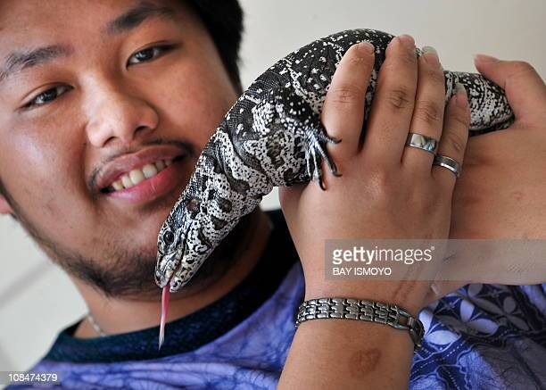 Filipino lizard owner Franky plays with his black and white tegu in Tanggerang on October 17 2010 AFP PHOTO / Bay ISMOYO