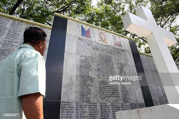 Filipino looks at names listed in memory of Filipino and US soldiers who died as prisoners of war from the Bataan Death March during World War II at...