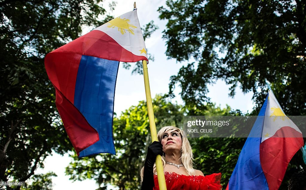A Filipino member of the LGBT community holds up the country's flag during a gay pride march calling for equal rights in Manila on June 25, 2016. / AFP / NOEL