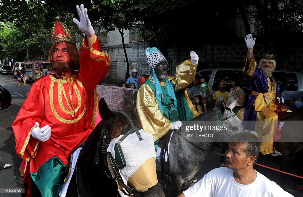 Filipino men dressed in costumes as the Three Kings parade along a street as they throw candy to children in Manila on January 4, 2015. The feast day, marking the visit of the Magi to the Child Jesus, is considered the official end of the Christmas season in the Philippines. Millions of Filipinos will be returning from Christmas vacation to school or work in the coming days. AFP PHOTO/Jay DIRECTO