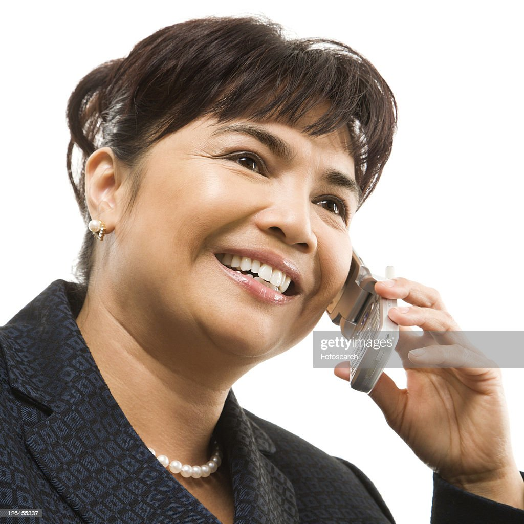 Filipino middle-aged businesswoman talking on cellphone against white background.