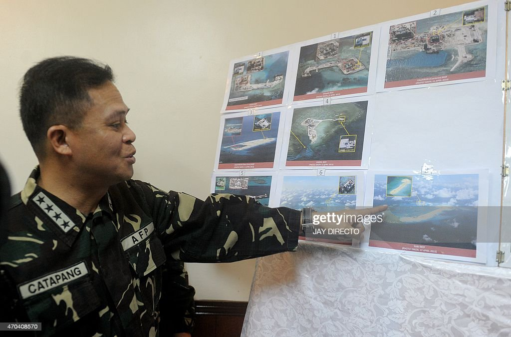 Filipino military chief General Gregorio Catapang points to aerial photos of Chinese construction over reefs and shoals in the Spratly archipelago...